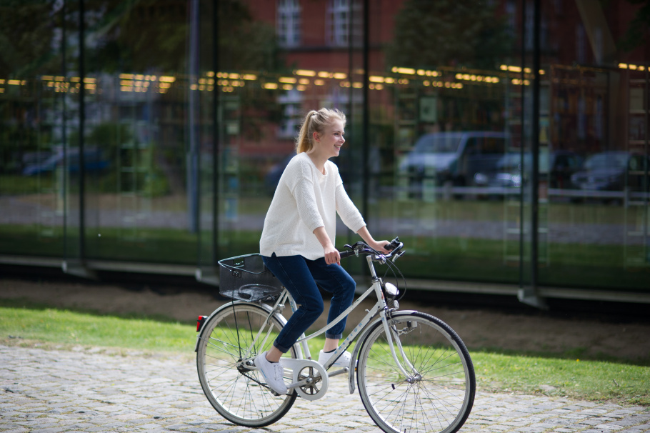 Girl on a bike riding along a campus building