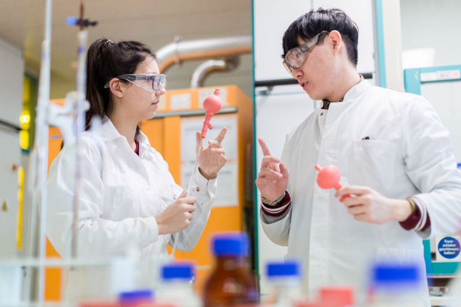 A female and a male student in lab coats