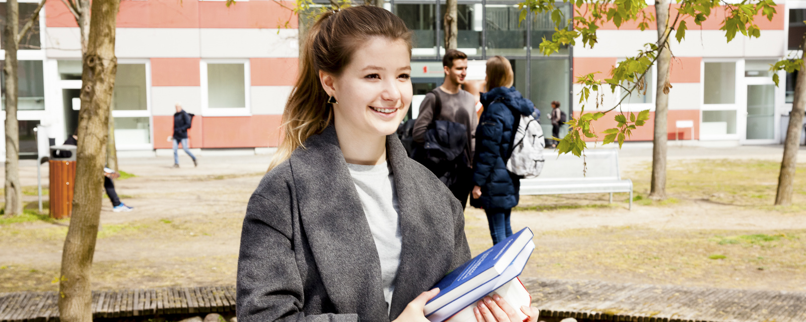 Female student carrying a book on campus