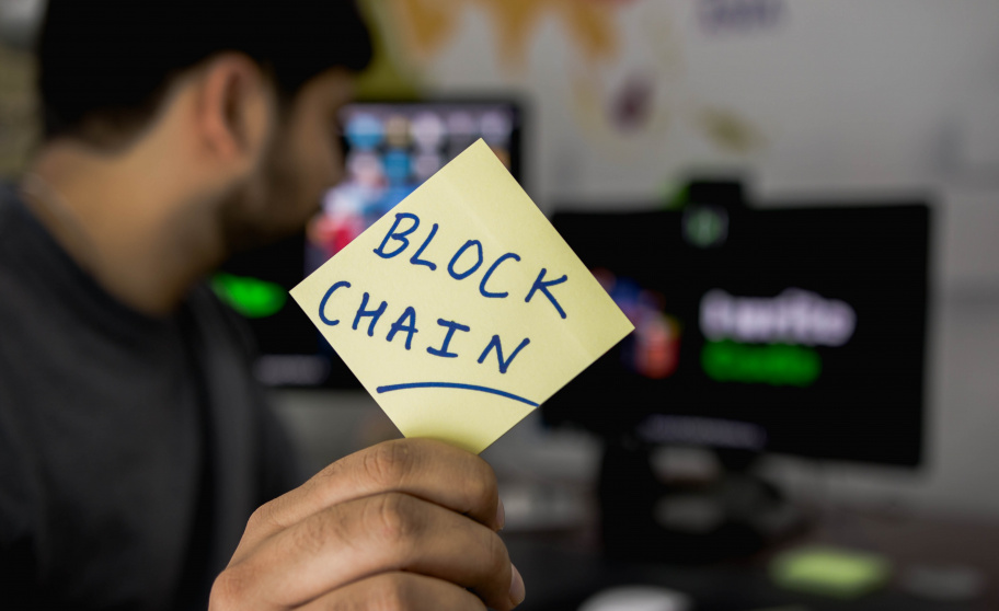 "Man holding a sticky note with ""Blockchain"" written on it"