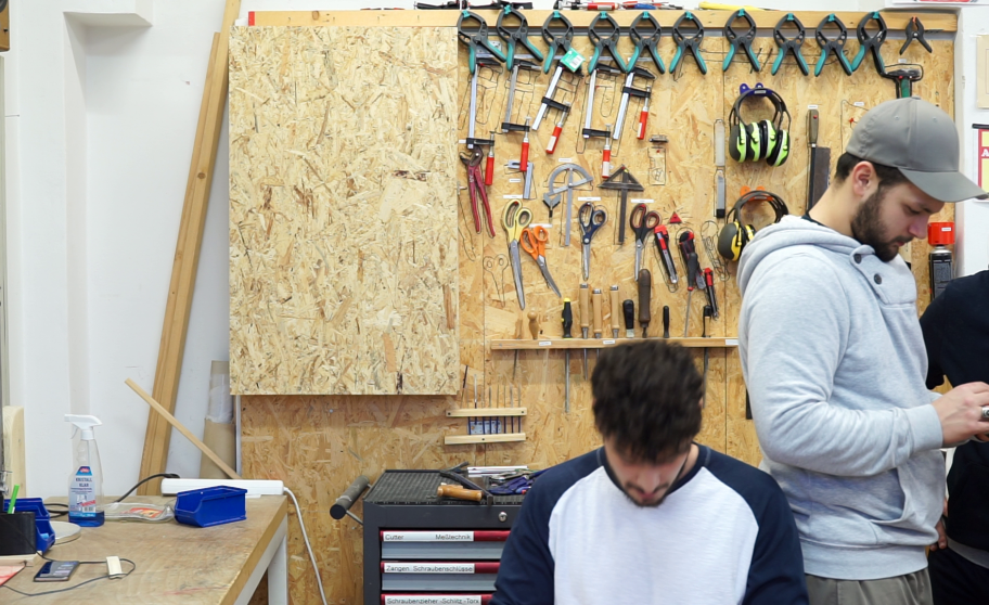 Two students in front of a wall with tools