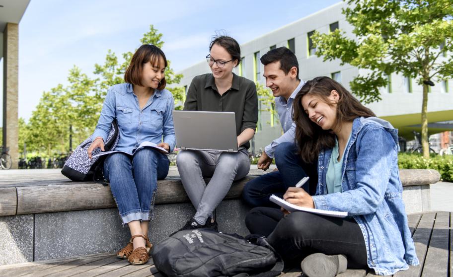 Students sitting outside with a laptop and notepad